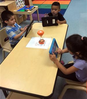 A group of children sitting at a table, and using tablet devices.