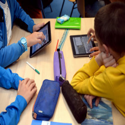 photo of children in a classroom with tablet devices.