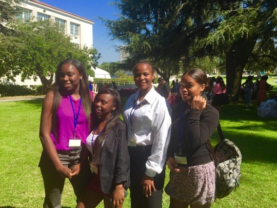 Female students and teacher attending leadership conference
