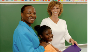 Two women and a student standing in front of a chalkboard